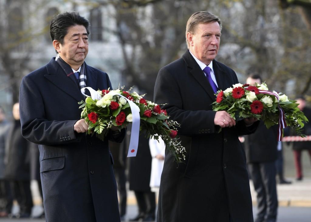 Japanese Prime Minister Shinzo Abe, left, and Latvian Prime Minister Maris Kucinskis lay flowers at the Freedom Monument in Riga, Latvia, Saturday, Ja