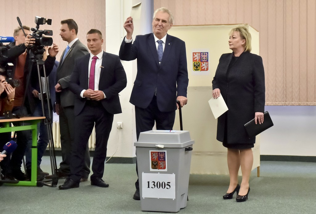 Presidential candidate and Czech President Milos Zeman shows his vote as his wife Ivana, right, looks on during the presidential election's first roun