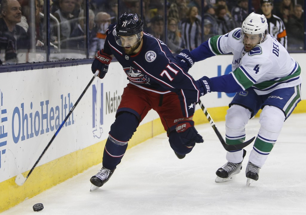 Columbus Blue Jackets' Nick Foligno, left, controls the puck as Vancouver Canucks' Michael Del Zotto defends during the second period of an NHL hockey
