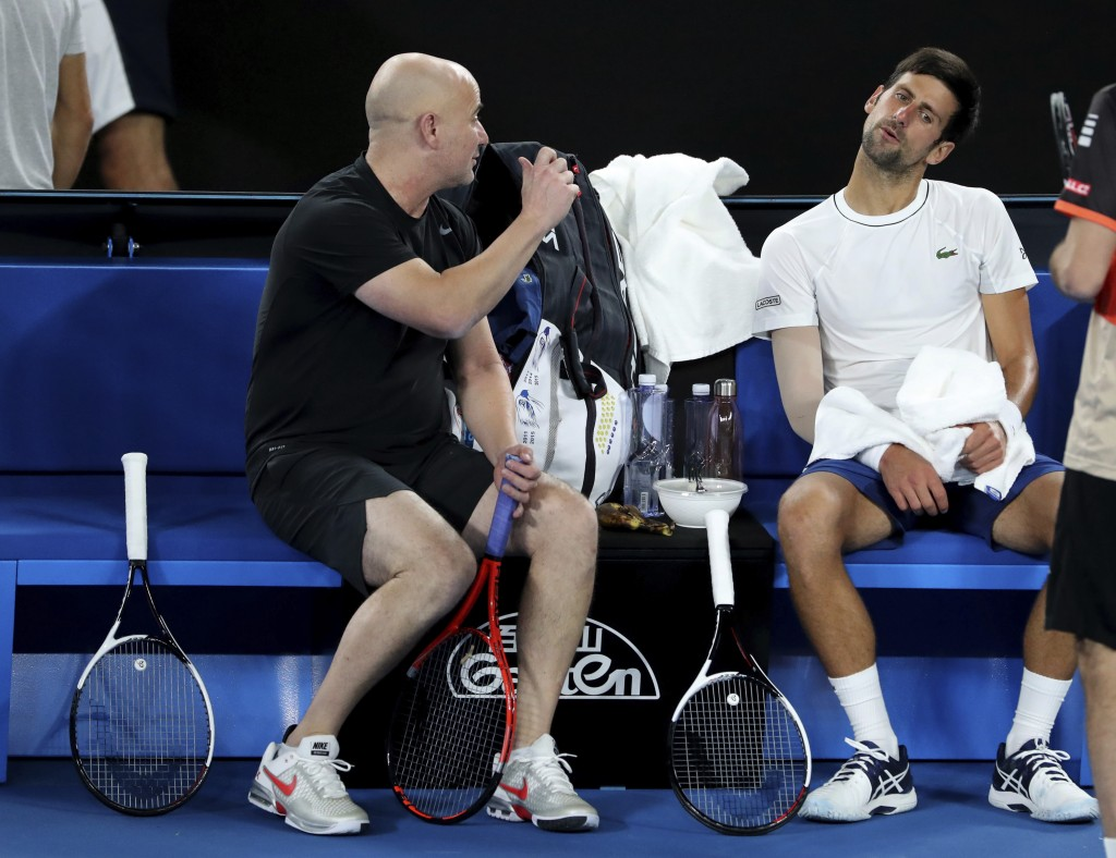 Serbia's Novak Djokovic talks with coach Andre Agassi, left, during a practice session ahead of the Australian Open tennis championships in Melbourne,