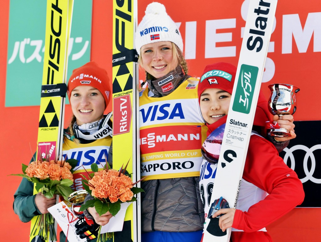 Maren Lundby of Norway, center, celebrates her win on the podium, along with second placed Germany's Katharina Althaus, left,  and third placed Japan'