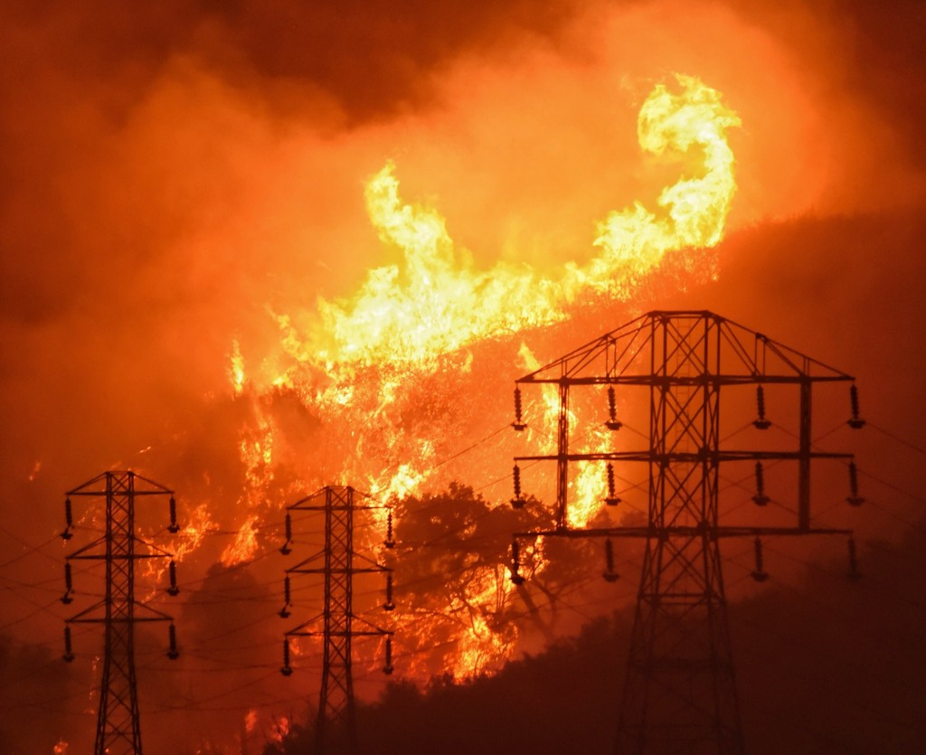 FILE - In this Saturday, Dec. 16, 2017, file photo provided by the Santa Barbara County Fire Department, flames burn near power lines in Sycamore Cany