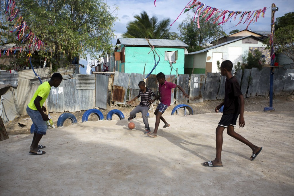 In this Wednesday, Jan. 10, 2018 photo, boys play a pickup game of soccer on a pitch carved out at the Caradeux refugee camp set up nearly eight years