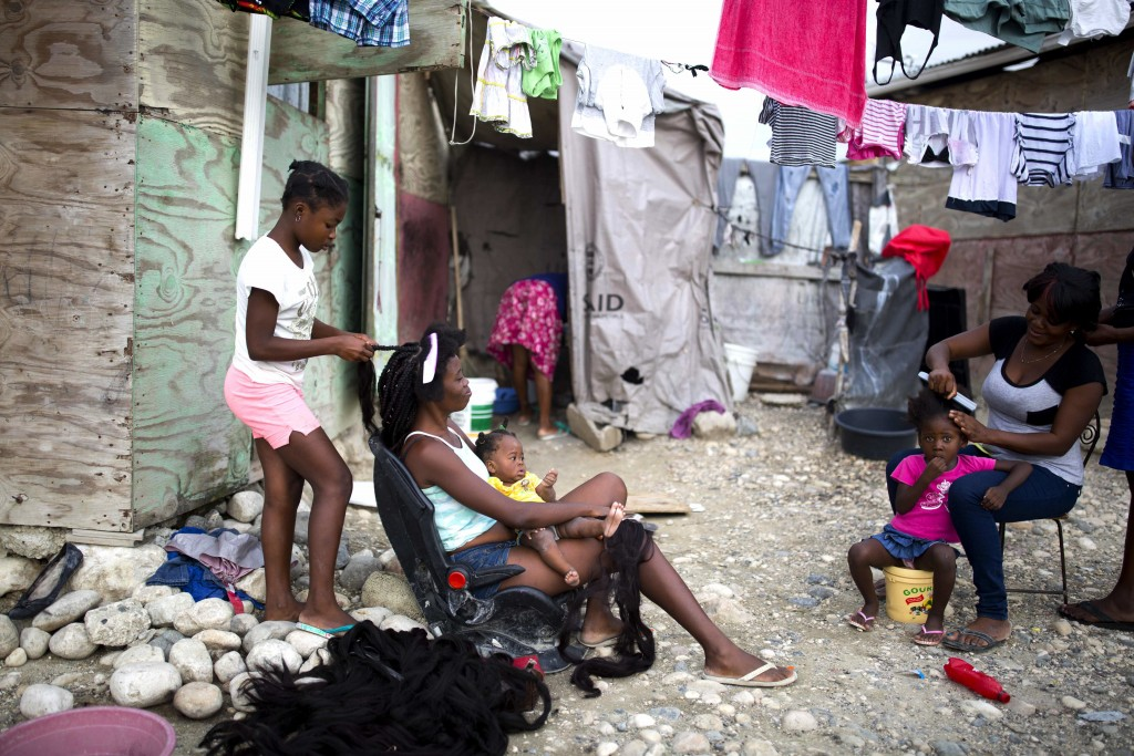 In this Saturday, Jan. 6, 2018 photo, 12-year-old Lima Veronise styles the hair of customer Resita Gilles, in the Caradeux refugee camp set up nearly