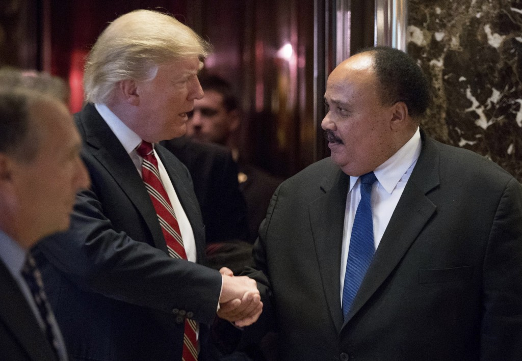 FILE- In this Jan. 16, 2017 file photo, President-elect Donald Trump shakes hands with Martin Luther King III, son of Martin Luther King Jr. at Trump