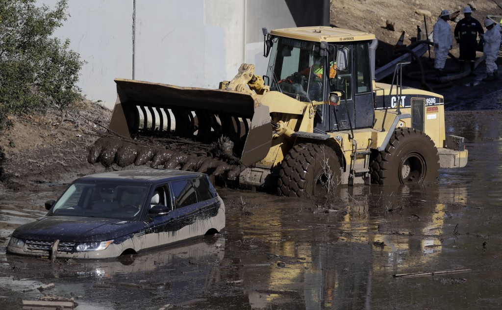 A work crew cleans up an area of Highway 101 that flooded in Montecito, Calif., Friday, Jan. 12, 2018. The number of missing after a California mudsli