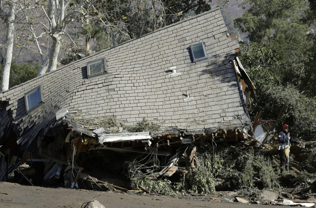 Emergency crew members search an area near houses damaged by storms in Montecito, Calif., Friday, Jan. 12, 2018. The number of missing after a Califor