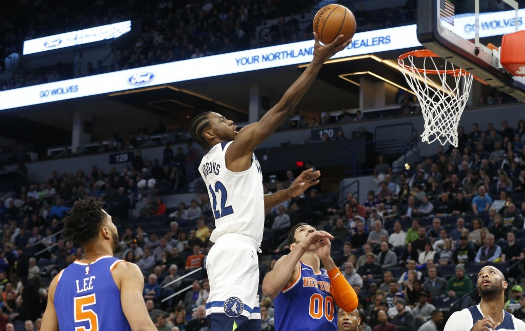 Minnesota Timberwolves' Andrew Wiggins, center, lays up a shot as New York Knicks' Courtney Lee, left, and Enes Kanter, of Turkey, watch in the first