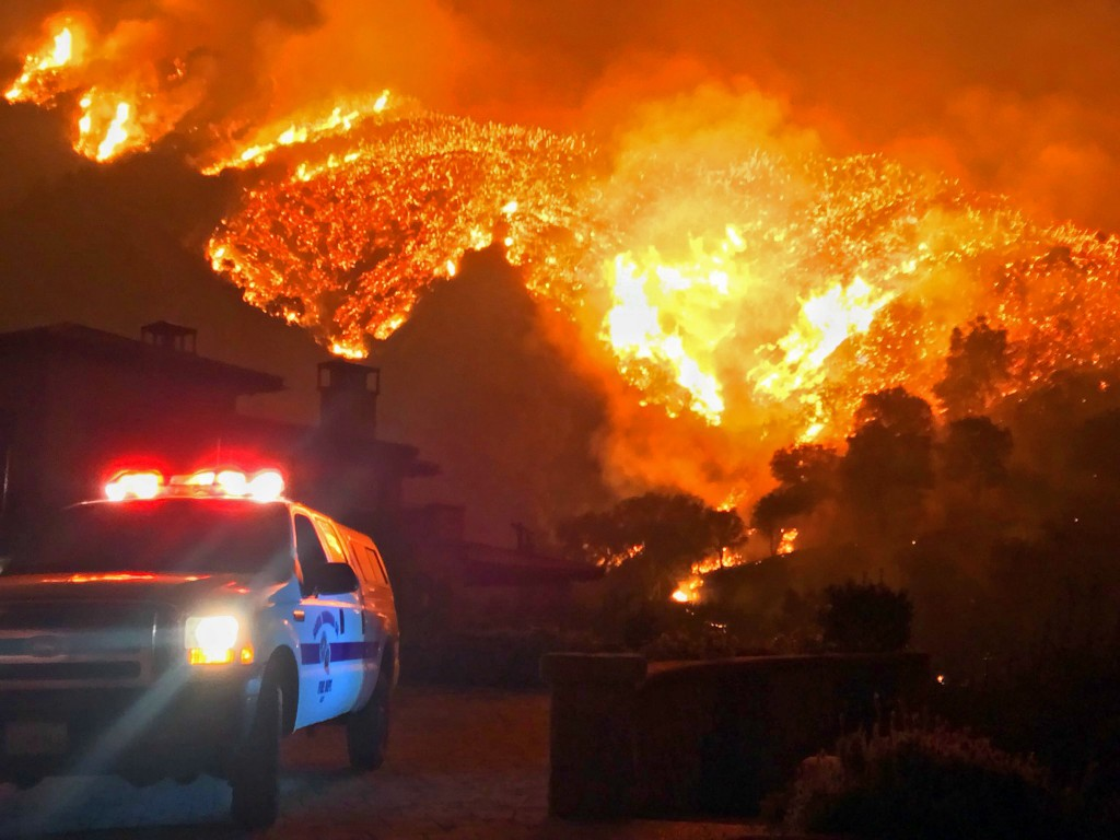 FILE - In this Dec. 12, 2017, file photo provided by the Santa Barbara County Fire Department, fire burns canyons and ridges above Bella Vista Drive n