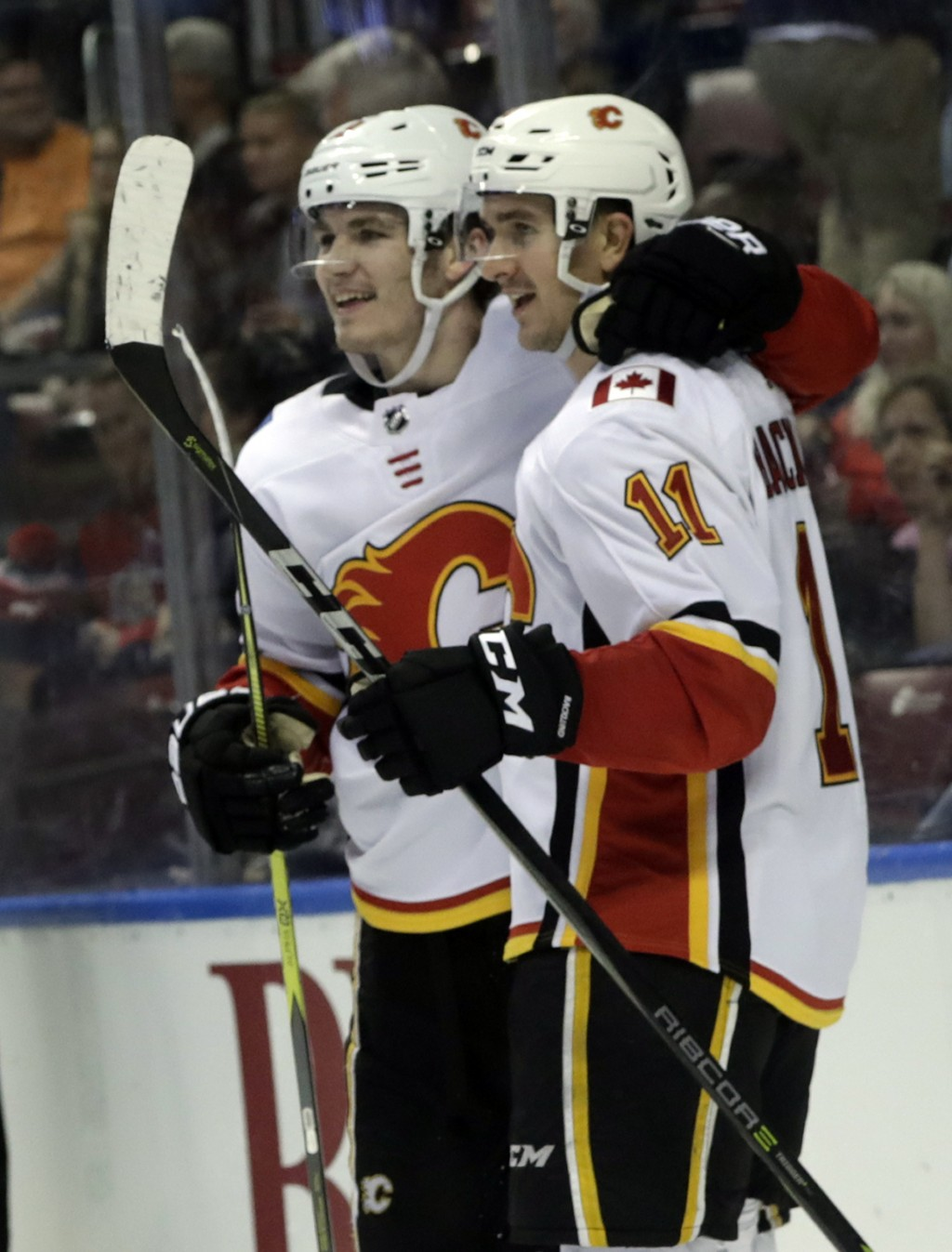 Calgary Flames' Mikael Backlund (11) is hugged by Matthew Tkachuk after scoring an empty-net goal during the third period of an NHL hockey game agains