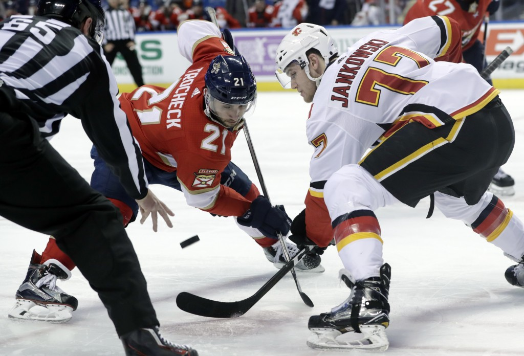 Florida Panthers' Vincent Trocheck (21) and Calgary Flames' Mark Jankowski (77) go for the puck during a faceoff during the second period of an NHL ho