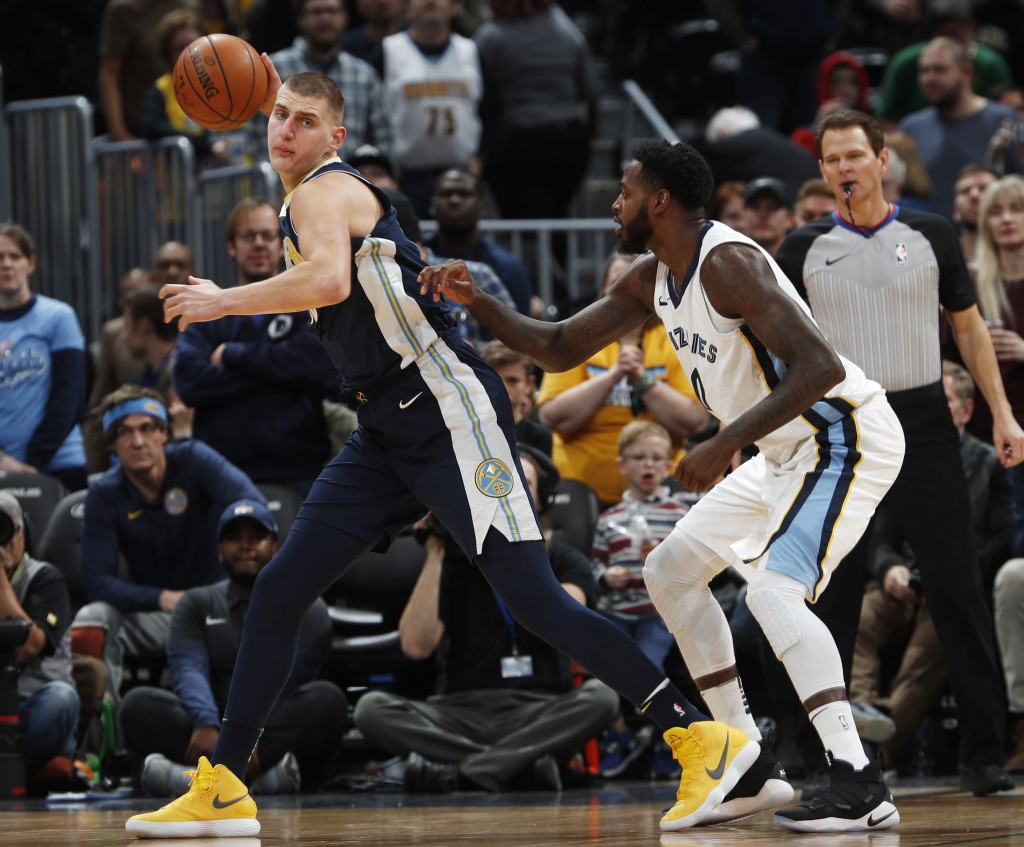 Denver Nuggets center Nikola Jokic, left, of Serbia, pulls in the ball as Memphis Grizzlies forward JaMychal Green defends in the first half of an NBA