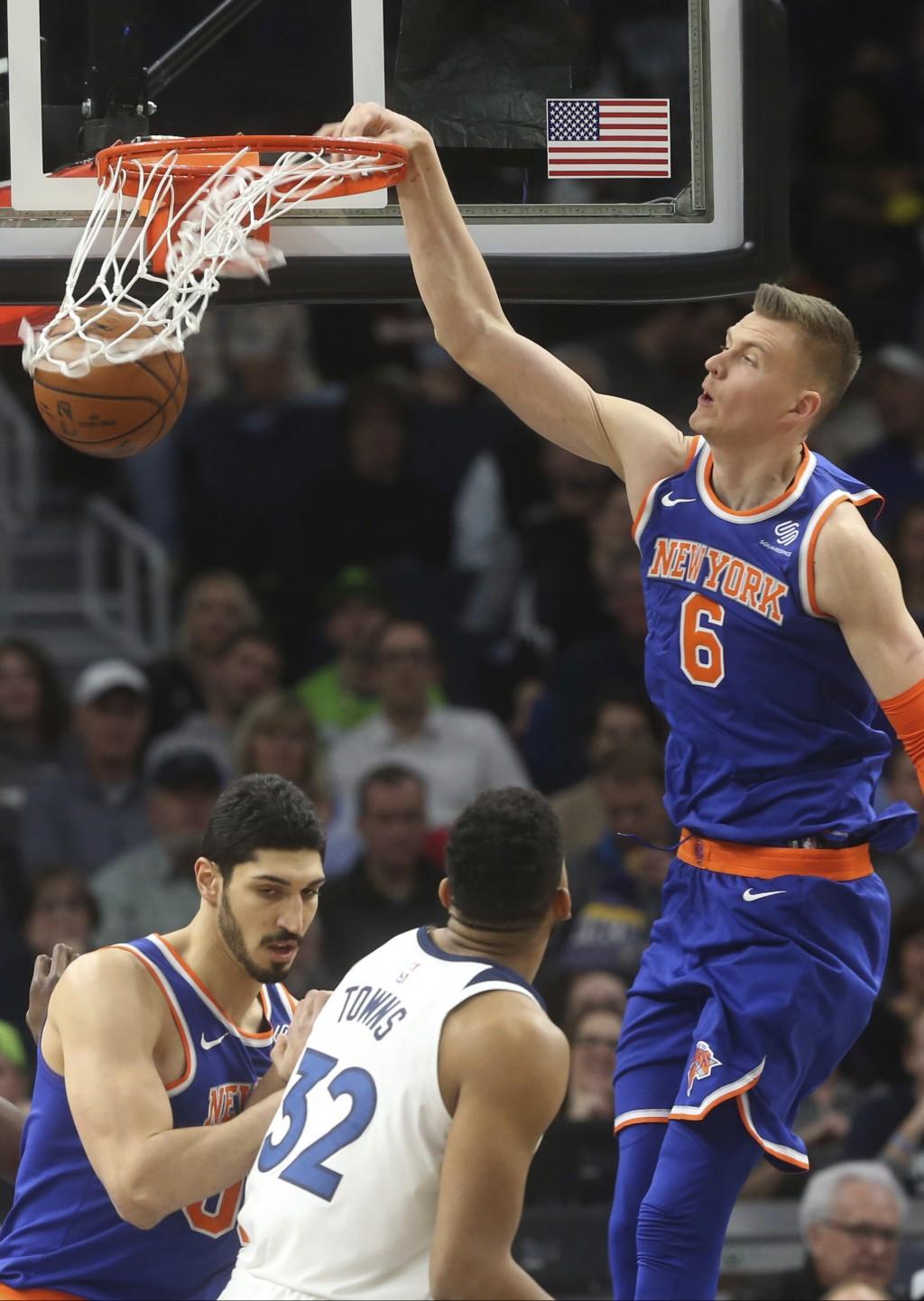 New York Knicks' Kristaps Porzingis (6), of Latvia, dunks as Minnesota Timberwolves' Karl-Anthony Towns, bottom, looks on in the first half of an NBA