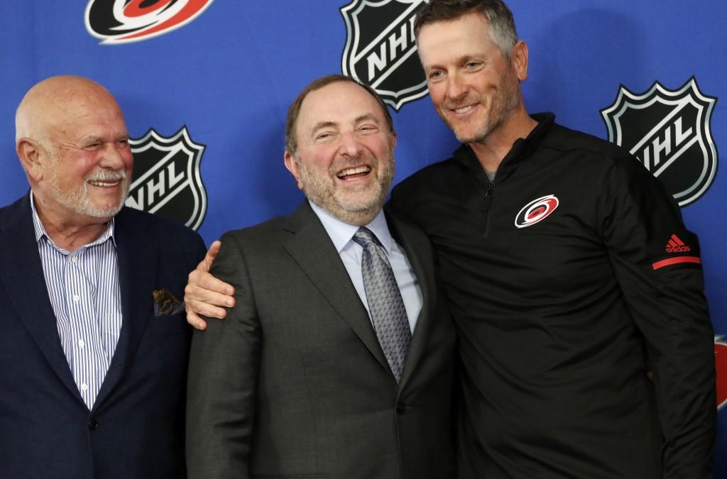 Former majority owner Peter Karmanos, left, NHL commissioner Gary Bettman, center, and Thomas Dundon, new majority owner of the Carolina Hurricanes NH