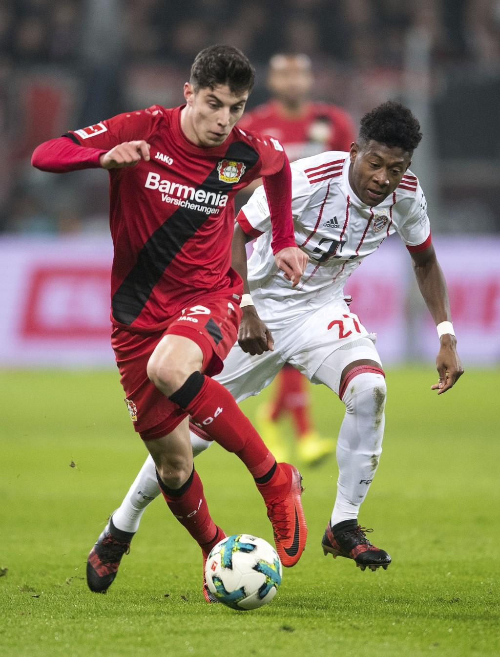 Leverkusen's Kai Havertz and Bayern's David Alaba, right, in action during the German Bundesliga soccer match between Bayer Leverkusen and Bayern Muni
