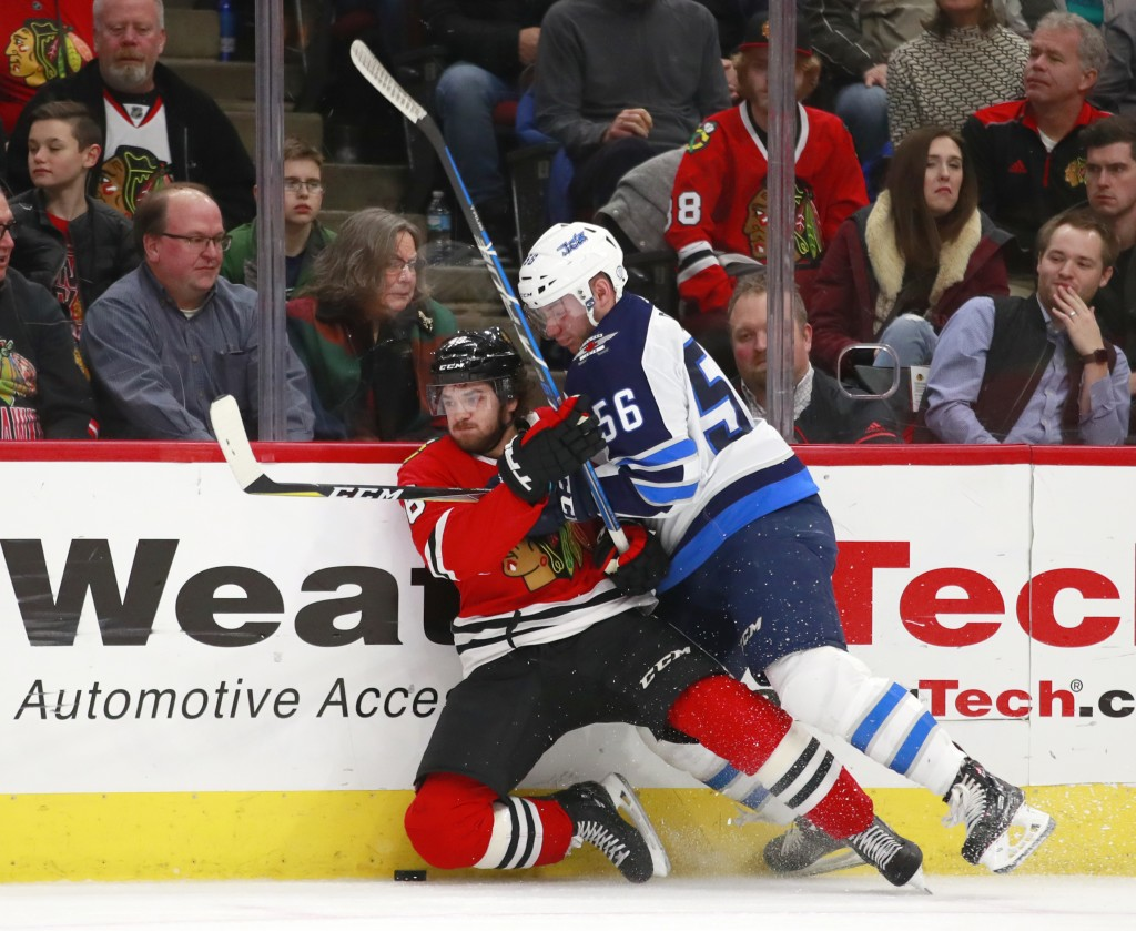 Winnipeg Jets center Marko Dano (56) checks Chicago Blackhawks left wing Vinnie Hinostroza (48) into the boards during the first period of an NHL hock