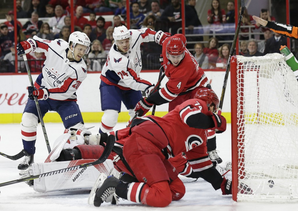 Washington Capitals' Lars Eller (20), of Denmark, assists as John Carlson (74) scores against Carolina Hurricanes goalie Cam Ward while Hurricanes' Ha
