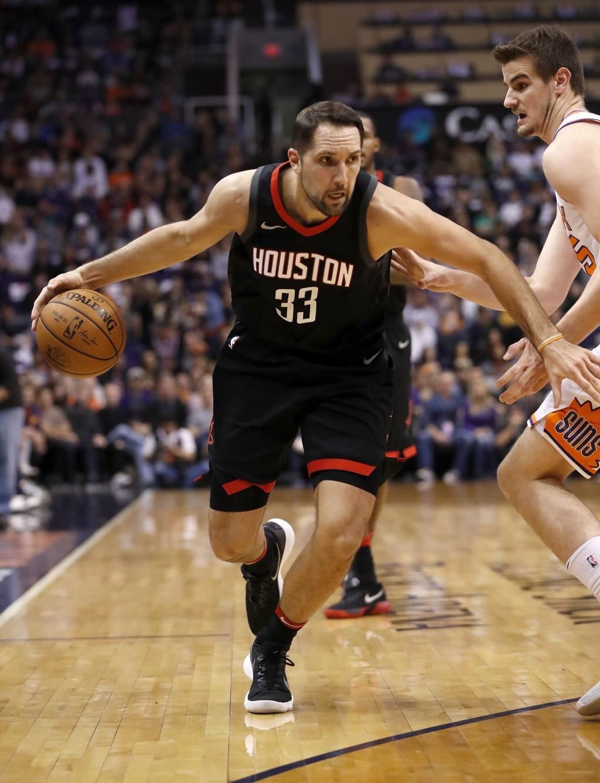Houston Rockets forward Ryan Anderson (33) drives past Phoenix Suns forward Dragan Bender during the first half of an NBA basketball game Friday, Jan.