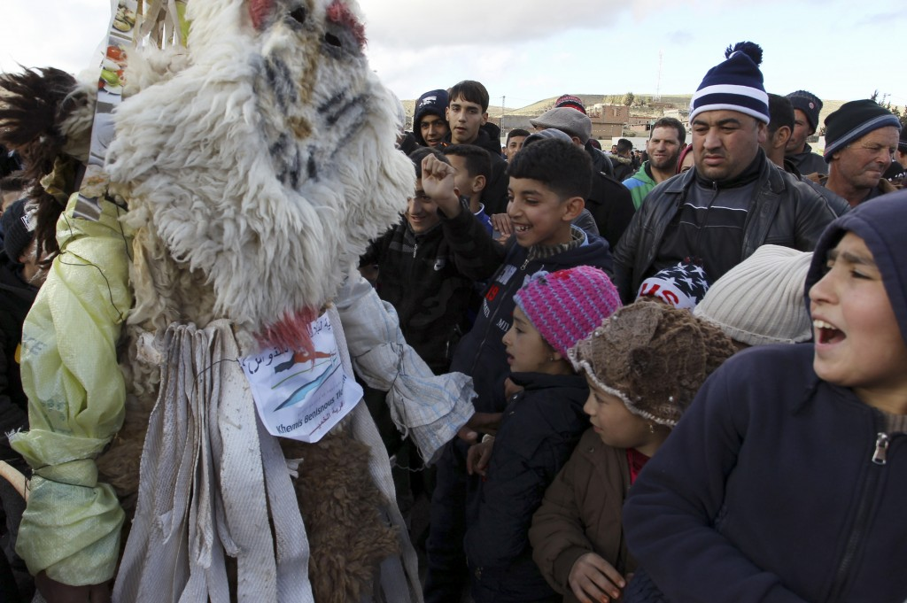 Performers dressed in animal-hide costumes greet children as part of the Ayred festival in the village of Beni Snous, south of Tlemcen, Algeria, Thurs