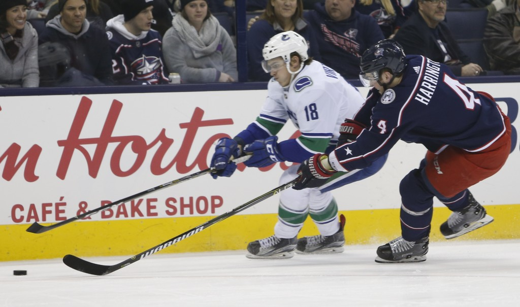Vancouver Canucks' Jake Virtanen, left, carries the puck upice as Columbus Blue Jackets' Scott Harrington defends during the first period of an NHL ho