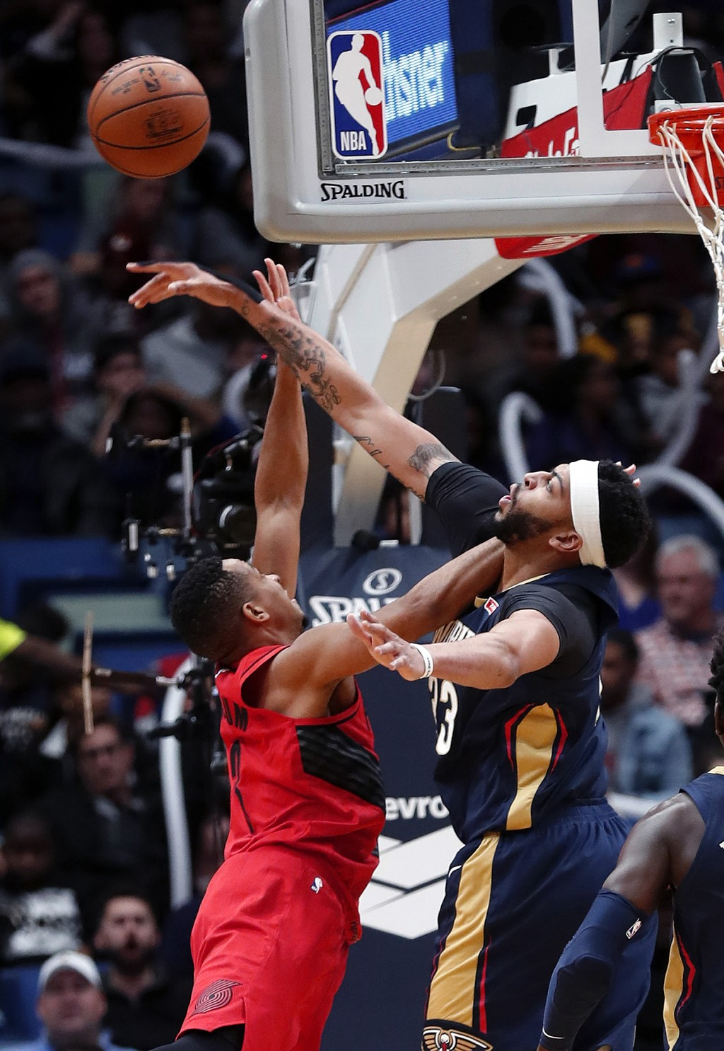 New Orleans Pelicans forward Anthony Davis, right, blocks a shot by Portland Trail Blazers guard CJ McCollum during the first half of an NBA basketbal