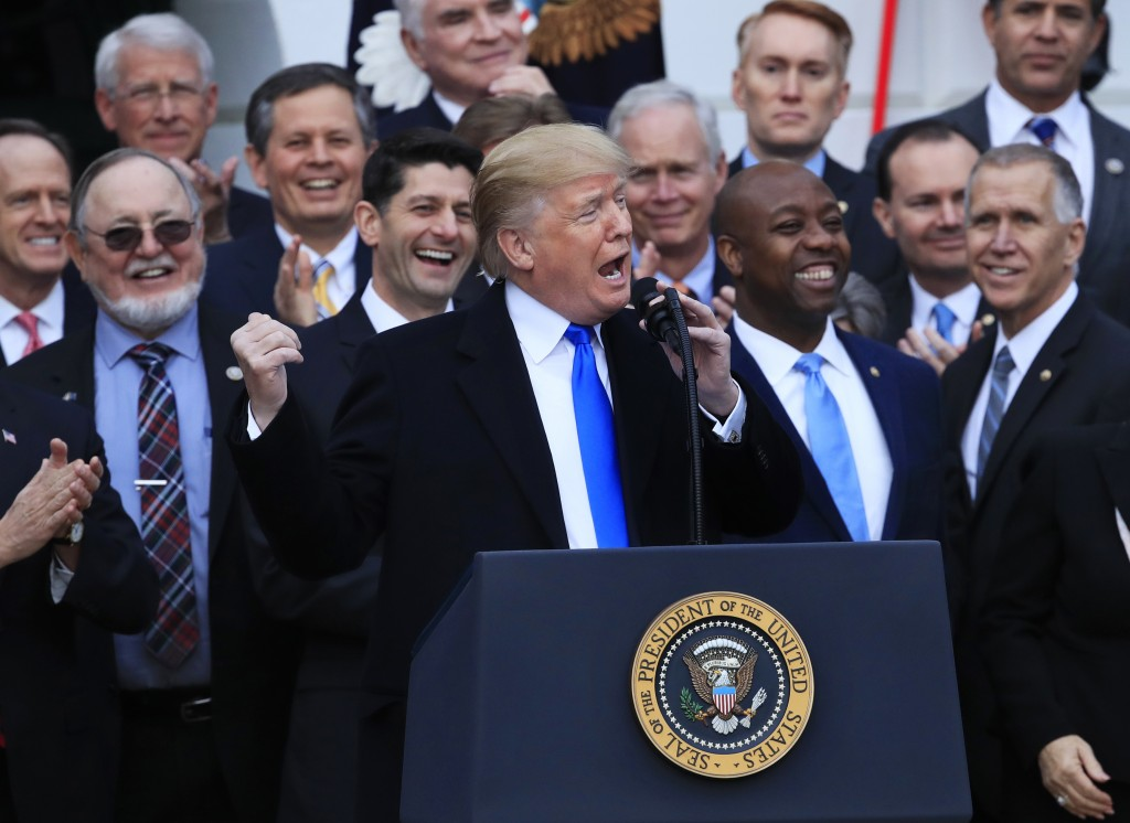 FILE - In this Dec. 20, 2017, file photo, House Speaker Paul Ryan of Wis., back left center, and other lawmakers react as President Donald Trump speak