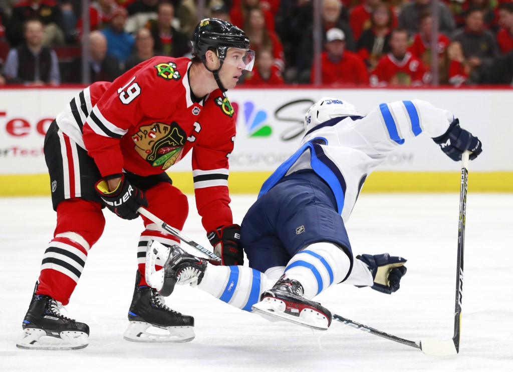 Chicago Blackhawks center Jonathan Toews (19) trips Winnipeg Jets center Marko Dano during the first period of an NHL hockey game Friday, Jan. 12, 201