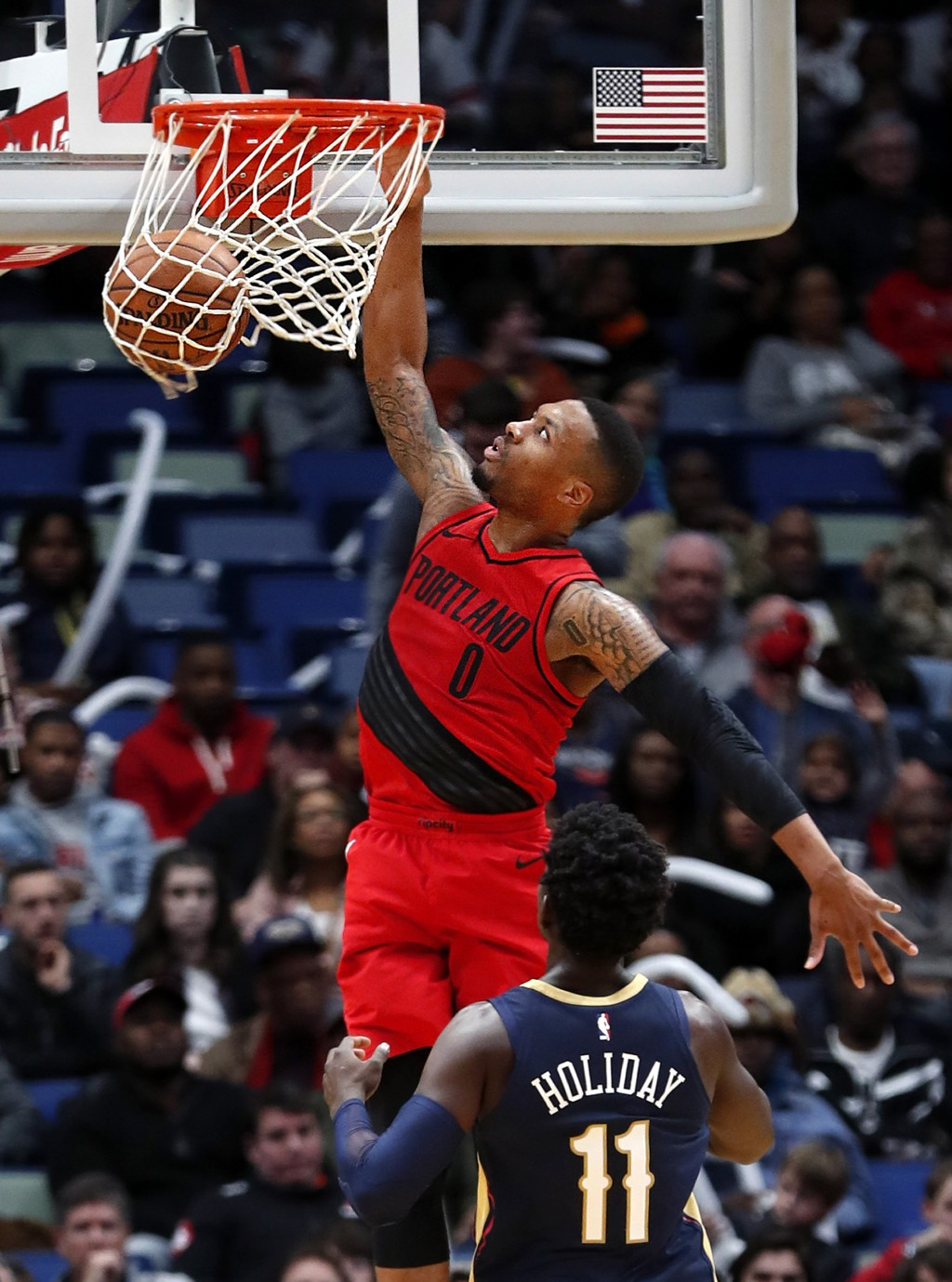 Portland Trail Blazers guard Damian Lillard (0) dunks over New Orleans Pelicans guard Jrue Holiday (11) during the first half of an NBA basketball gam
