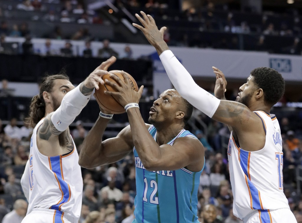 Charlotte Hornets' Dwight Howard, center, drives between Oklahoma City Thunder's Paul George, right, and Steven Adams, left, during the first half of
