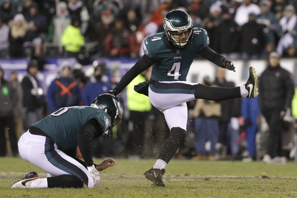 Philadelphia Eagles' Jake Elliott, right, kicks a field goal as Donnie Jones holds during the first half of an NFL divisional playoff football game ag