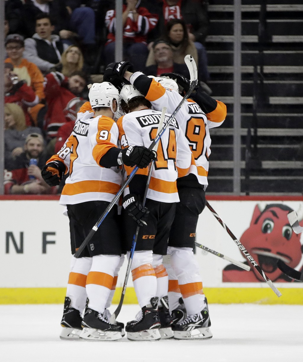 Philadelphia Flyers players celebrate a goal by Sean Couturier (14) against the New Jersey Devils during the second period of an NHL hockey game, Satu