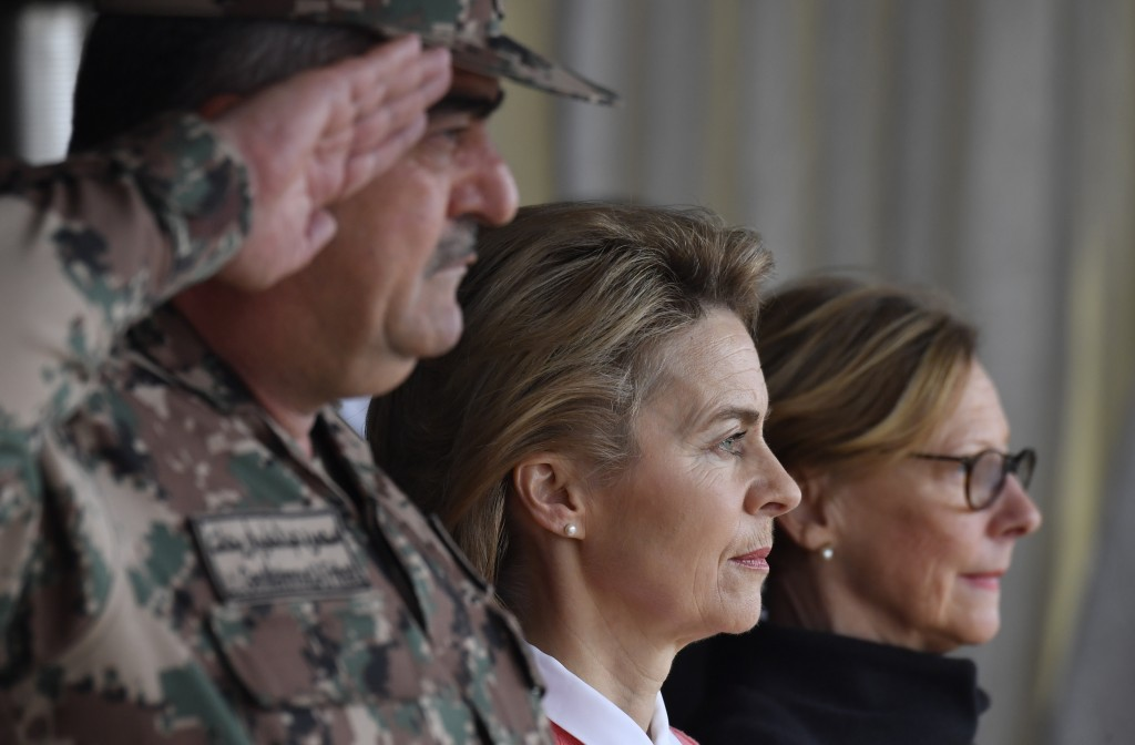 German Defence Minister Ursula von der Leyen, center, and Jordanian Chairman of the Joints Chief of Staff Mahmoud Freihat, left, listen to national an