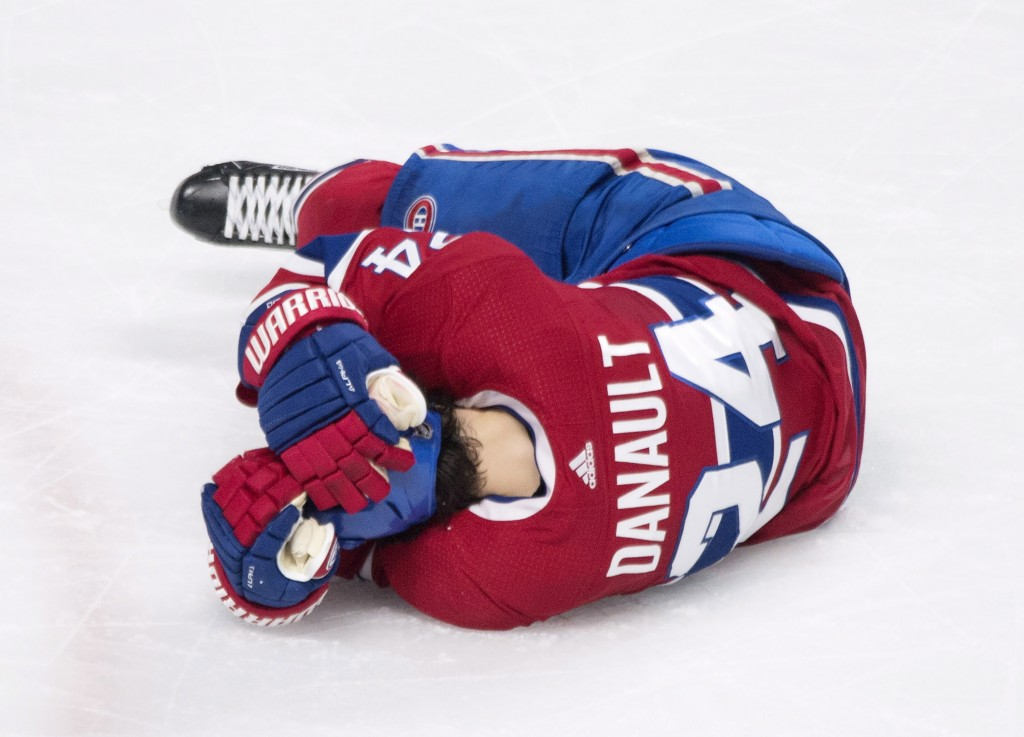 Montreal Canadiens' Phillip Danault lies injured on the ice after he was hit in the head by a puck on a shot by Boston Bruins' Zdeno Chara during seco
