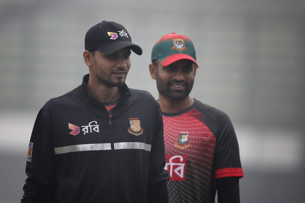 Bangladesh's cricket team captain Mashrafe Mortaza, left, and teammate Tamim Iqbal walk on the field during a training session ahead of the Tri-Nation