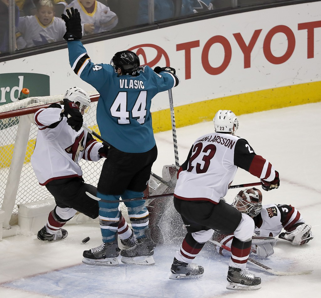 San Jose Sharks defenseman Marc-Edouard Vlasic (44) celebrates after scoring a goal past Arizona Coyotes center Christian Dvorak, left, in overtime of