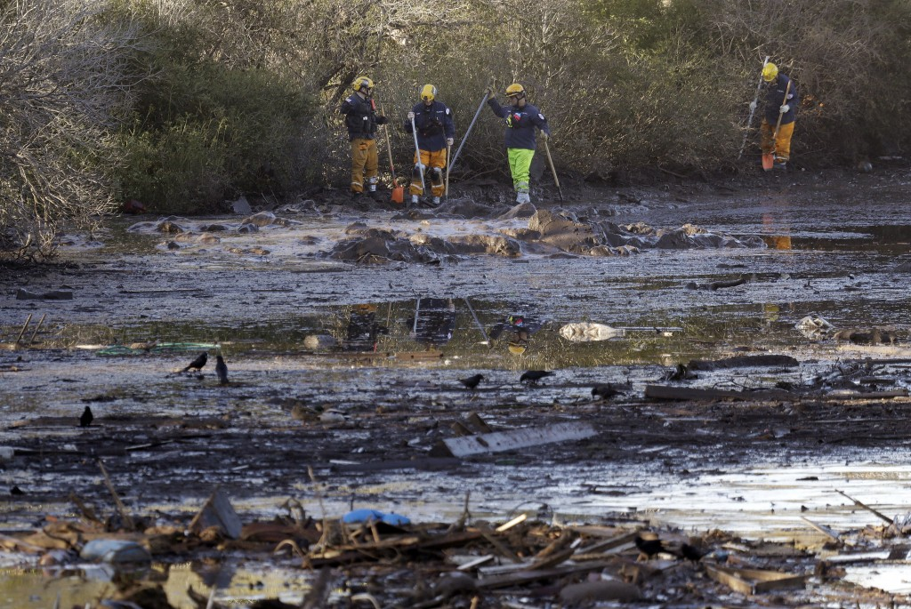 Search and rescue crews walk along the mud-covered southbound lanes of Highway 101 Saturday, Jan. 13, 2018, in Montecito, Calif.  Most of the people o