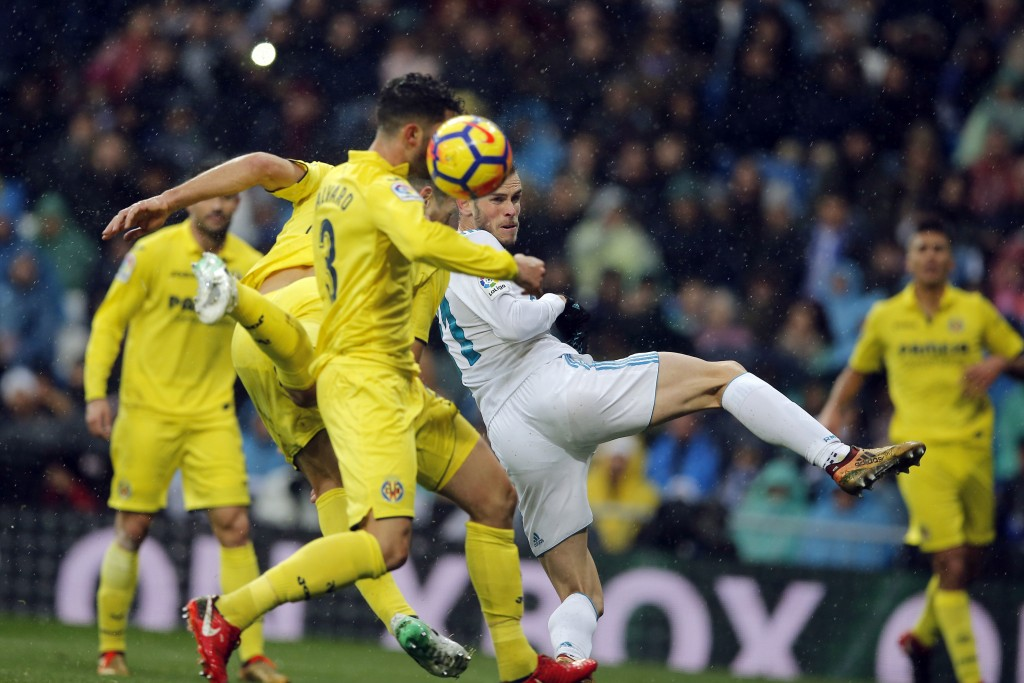 Real Madrid's Gareth Bale, centre and Villarreal's Alvaro Gonzalez go for a header in the goalmouth during a Spanish La Liga soccer match between Real