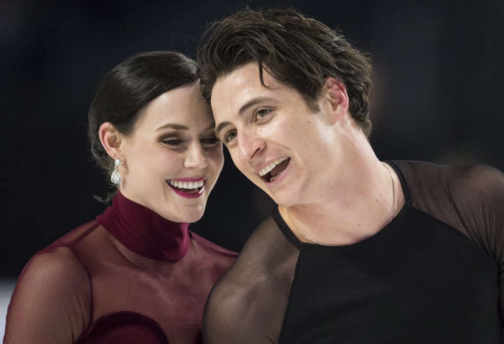 Tessa Virtue, left, and Scott Moir skate off the ice after their free dance performance in the ice dancing competition at the Canadian Figure Skating