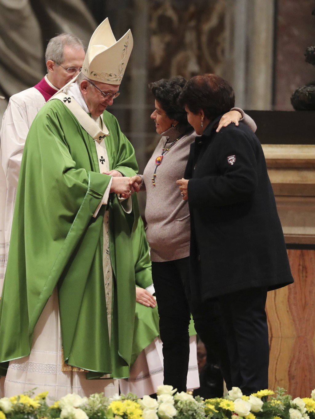 Women greets Pope Francis during the offertory on the occasion of a Mass on the world day for migrants and refugees, in St. Peter's Basilica at the Va