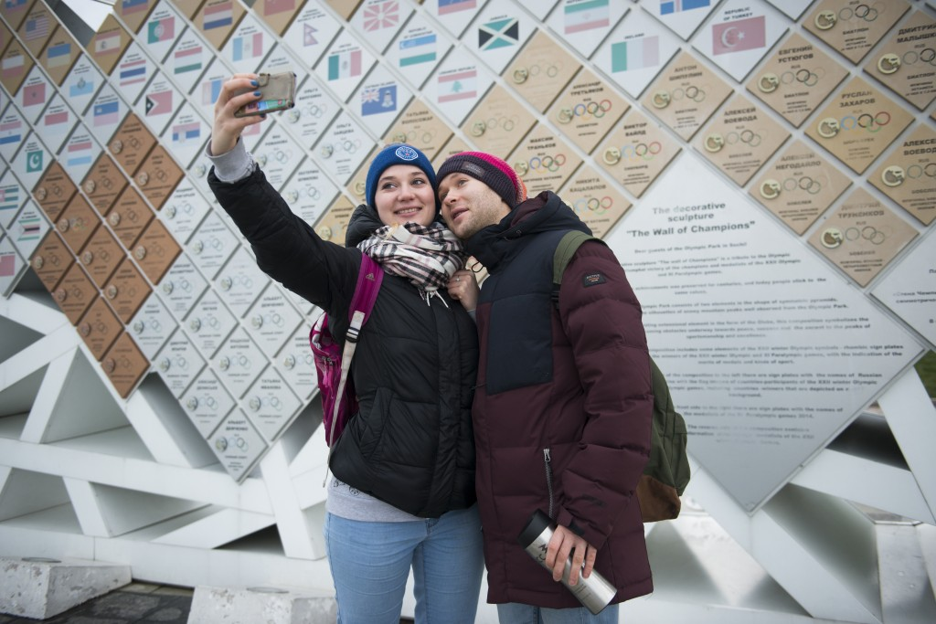 In this photo taken on Friday, Jan. 12, 2018, two visitors take a selfie in front of a board in the Olympic Park in Sochi displaying the names of 2014