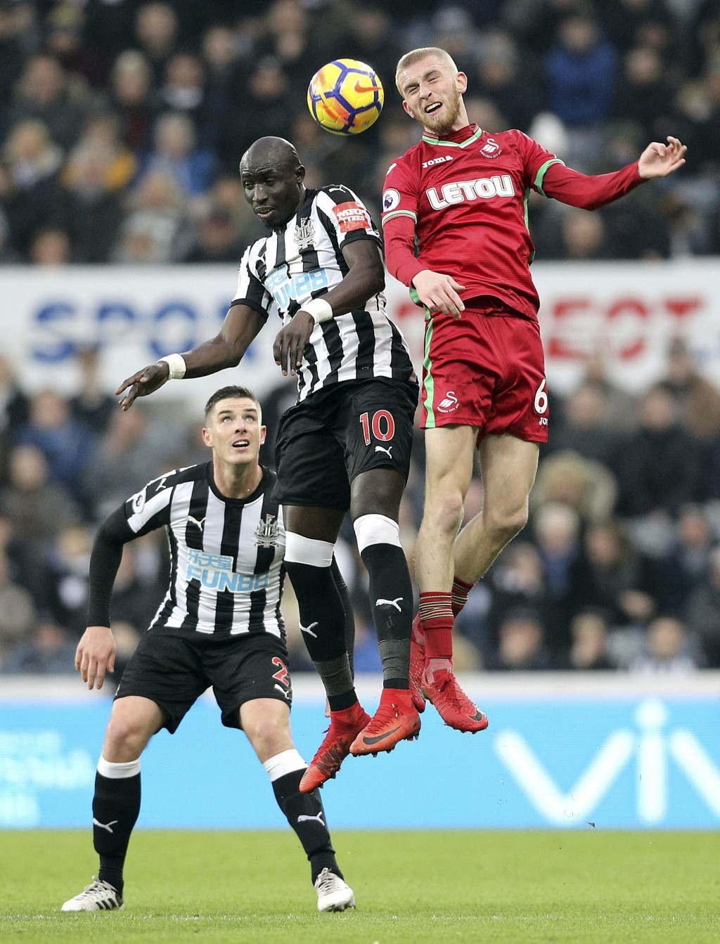 Newcastle United's Mohamed Diame, center, and Swansea City's Oliver McBurnie battle for a header during the English Premier League soccer match agains