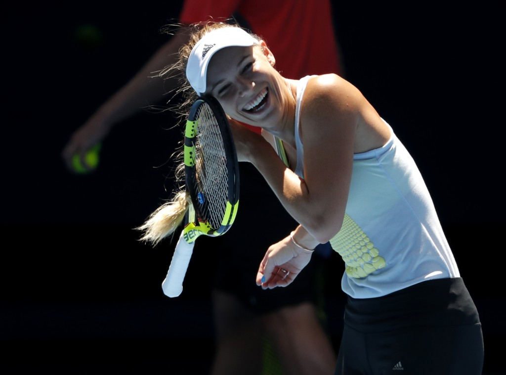 Denmark's Caroline Wozniacki reacts as her hair is tangled in her racket during a practice session ahead of the Australian Open tennis championships i