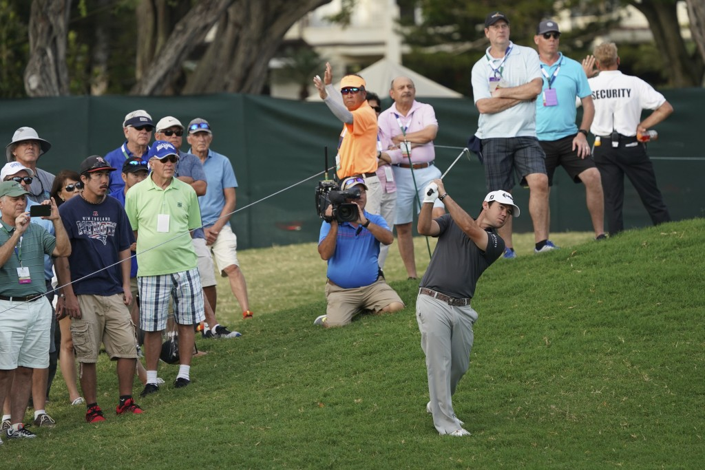 Brian Harman, center right, hits his ball back onto the 16th fairway during the third round of the Sony Open golf tournament, Saturday Jan. 13, 2018,