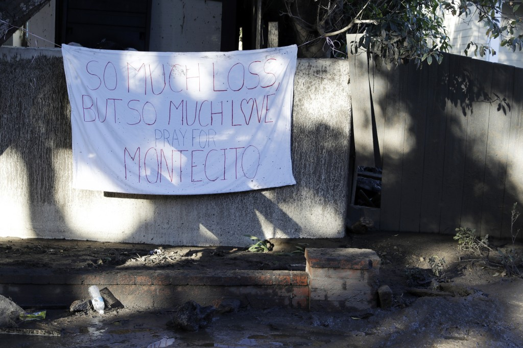 A sign is placed on a fence in the aftermath of a devastating mudslide Saturday, Jan. 13, 2018, in Montecito, Calif.  Most of the people of Montecito,