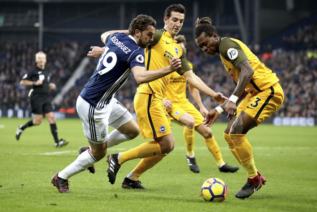 West Bromwich Albion's Jay Rodriguez, left, battles for the ball with Brighton & Hove Albion's Lewis Dunk and Gaetan Bong, right, during the English P