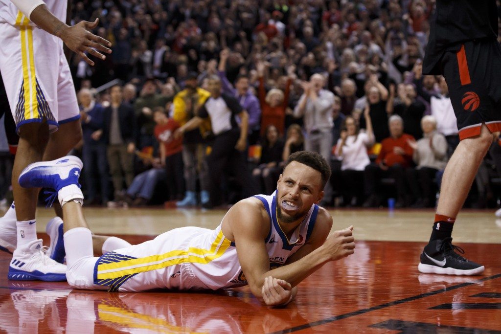 Golden State Warriors guard Stephen Curry (30) lies on the court after being fouled during the second half of the team's NBA basketball game against t