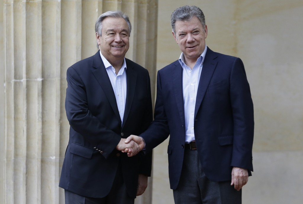 U.N. Secretary-General Antonio Guterres, left, and Colombia's President Juan Manuel Santos, shake hands as they pose for photos during a welcoming cer