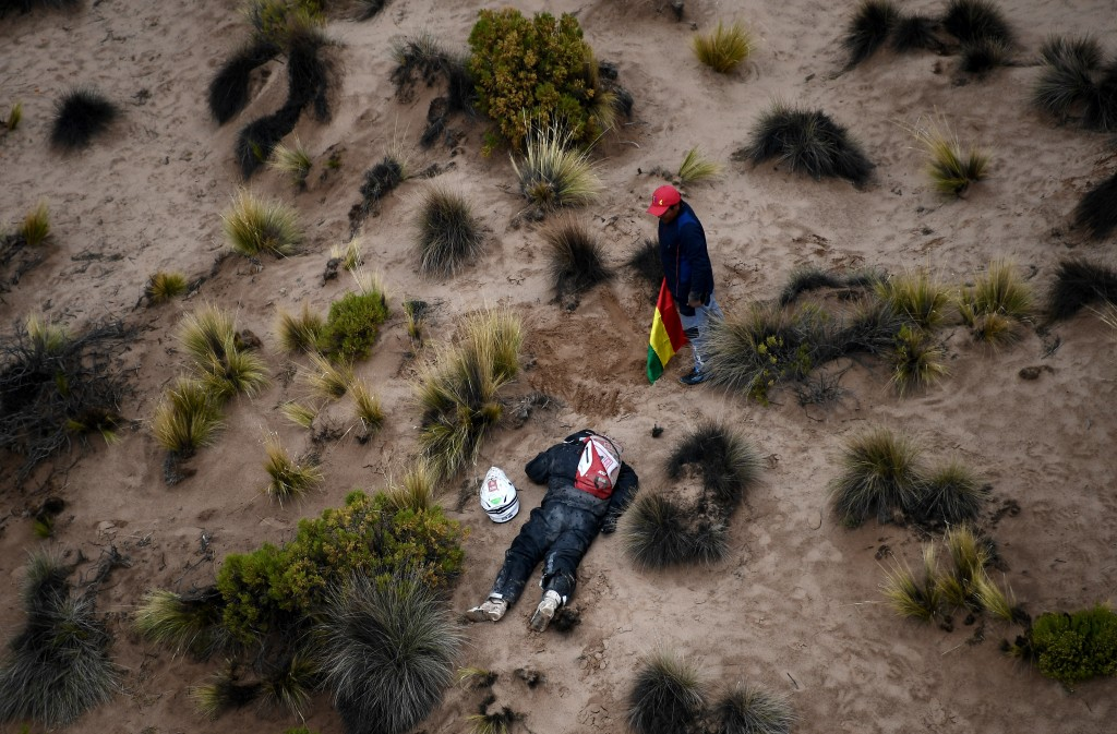 A spectator stand next to Guillaume Martens, of Netherlands, after he fell from his KTM motorbike during stage 7 of the 2018 Dakar Rally between La Pa