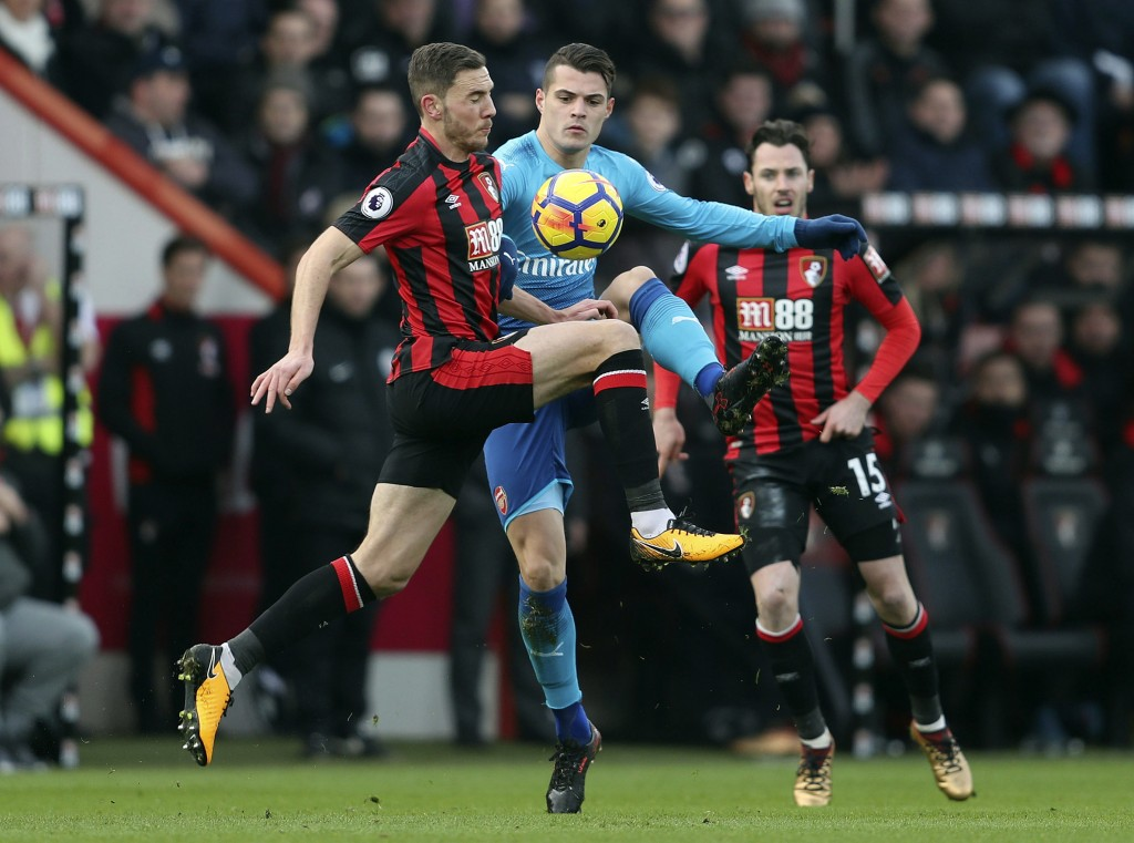 Arsenal's Granit Xhaka, center, is challenged by Bournemouth's Dan Gosling during the English Premier League soccer match against Bournemouth at the V