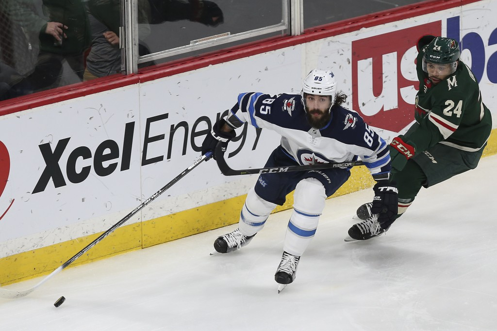 Winnipeg Jets' Mathieu Perreault (85) controls the puck in front of Minnesota Wild's Matt Dumba (24) in the first period of an NHL hockey game Saturda